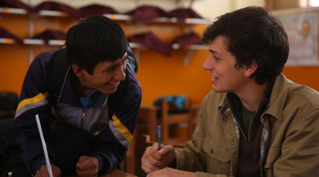 Maestro voluntario habla con uno de sus estudiantes en su voluntariado de educación en Perú.